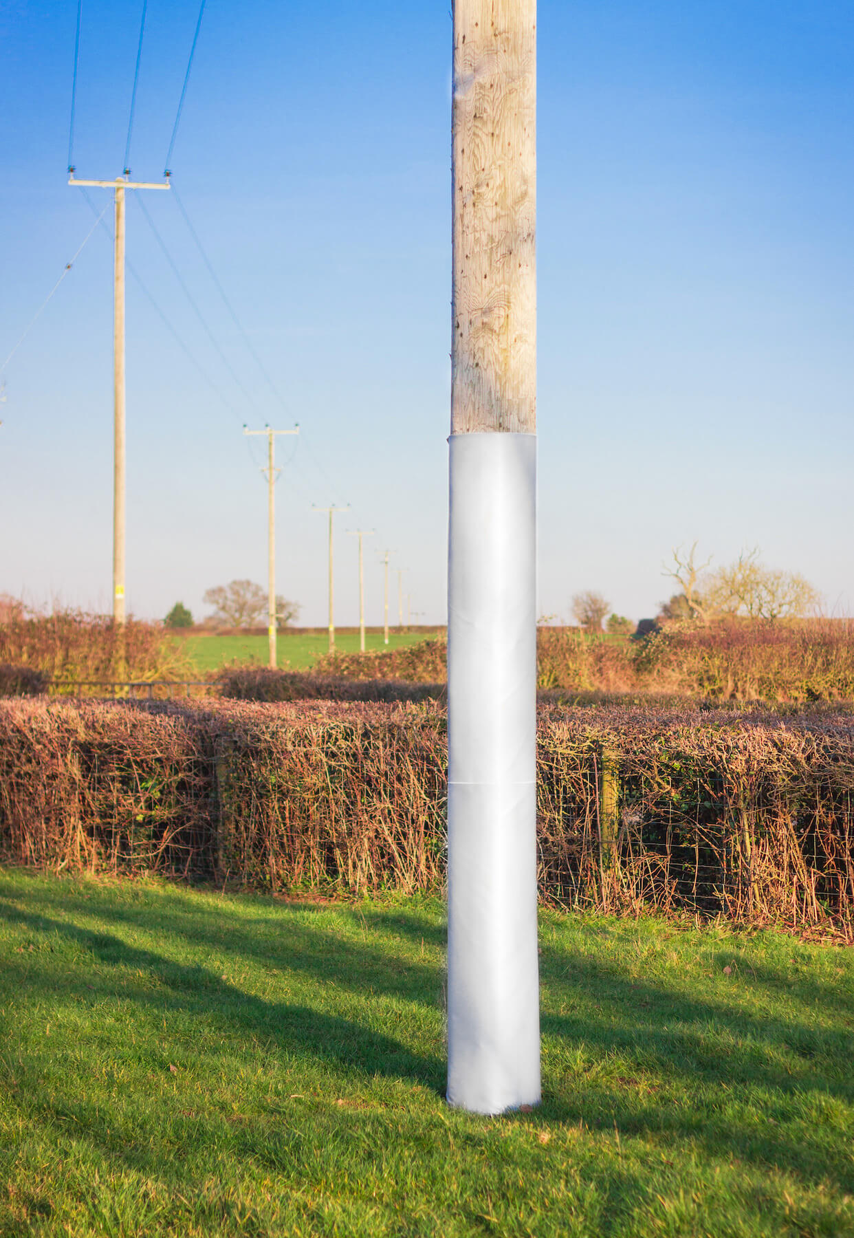 Polesaver fire fabric shown on a wooden utility pole in field